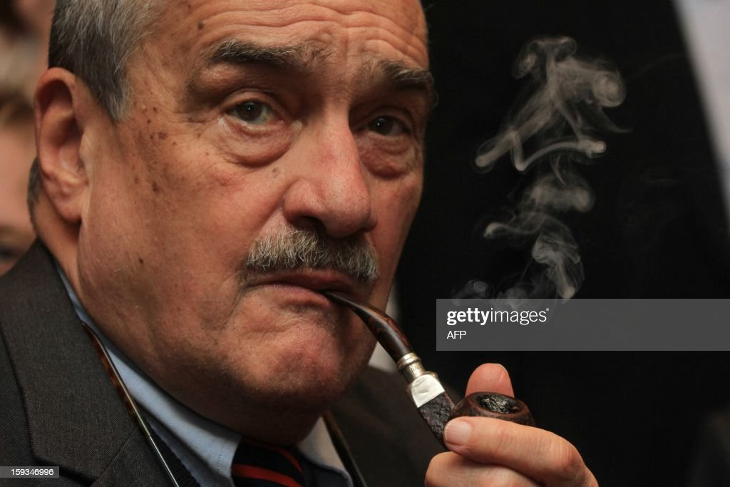 Czech Foreign Minister Karel Schwarzenberg smokes a pipe as he waits for the results of the presidential elections in Prague, on January 12, 2013.The pipe-smoking Schwarzenberg, chairman of the right-wing governing coalition TOP 09 party, has promised to quit his party if elected president.AFP PHOTO / RADEK MICA