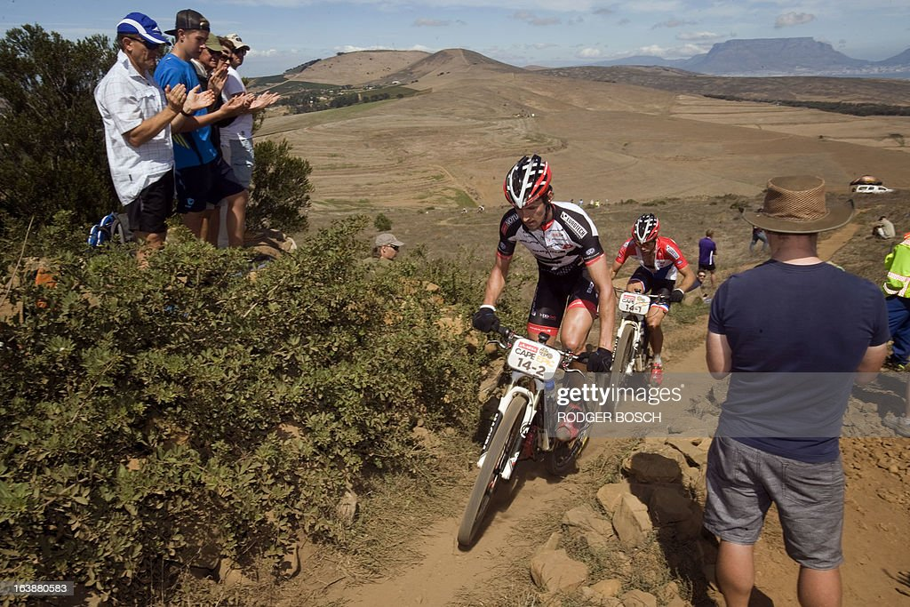 Czech Jiri Novak (L) and Dutch Hans Becking ride up a hill on March 17, 2013 during the prolog stage of the 2013 Cape Epic Mountain Bike Race at the Meerendal Wine estate, about 30 kms from Cape Town. The eight-day race covers a distance of more than 800 kms, climbing more than 15,000 meters. AFP PHOTO / RODGER