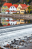 Czech Republic, Czech Krumlov. Traditional houses over river. Picturesque landscape with waterfall.