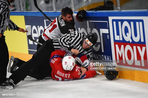 Czech linesman Libor Suchanek places himself between Canada's forward Alex Killorn and Norway's forward Niklas Roest during the IIHF Men's World...