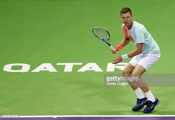 Czech player Tomas Berdych returns the ball to Italy's Alessandro Giannessi on the fourth day of the ATP Qatar Open tennis competition in Doha on...