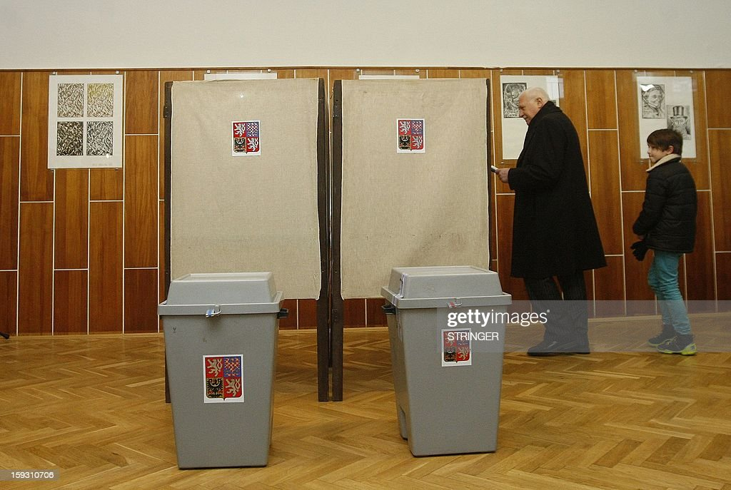 Czech President Vaclav Klaus walks behind a curtain at a polling station in Prague on January 11, 2013. Czech polling stations opened on January 11 afternoon in local mid-time for the first round of the first Czech direct presidential election in history.