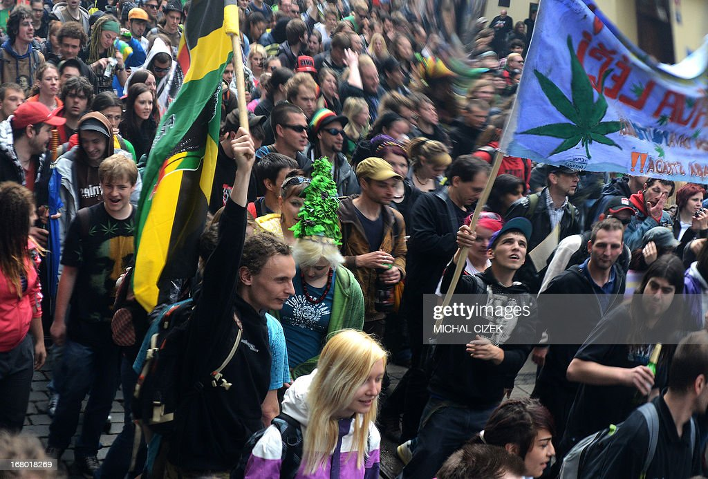 Czech protester are reflected in a mirror as they take part in a demonstration for the legalization of marijuana, in Prague on May 4, 2013.