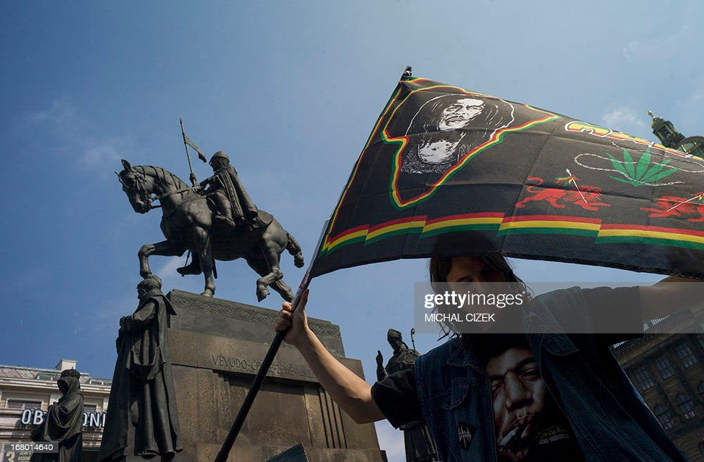 A Czech protester holds a flag with the face of Bob Marley in front of the Saint Venceslas Statue as he takes part in a march calling for the legalization of marijuana, in Prague on May 4, 2013.