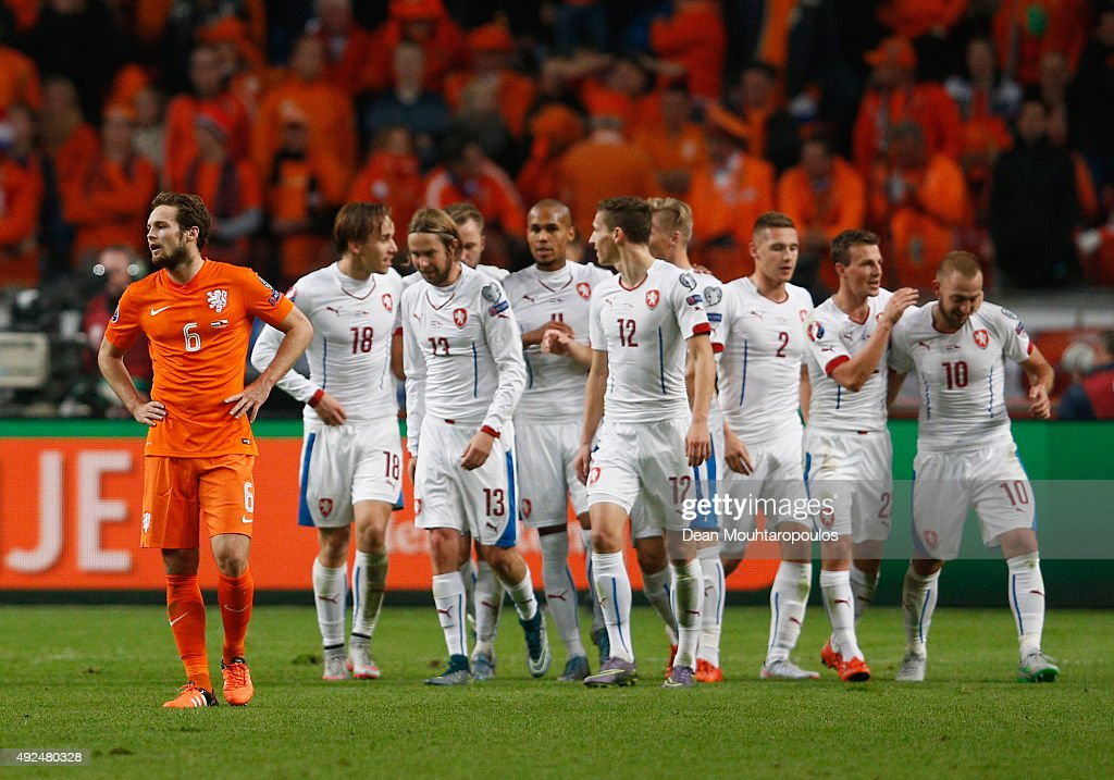 Czech Republic players celebrate as Daley Blind of the Netherlands looks dejected as Robin van Persie of the Netherlands scores an own goal for the...