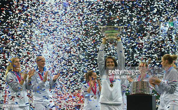 Czech Republic's Fed Cup team player Lucie Safarova holding the trophy of the International Tennis Federation Fed Cup celebrates with her teammates...