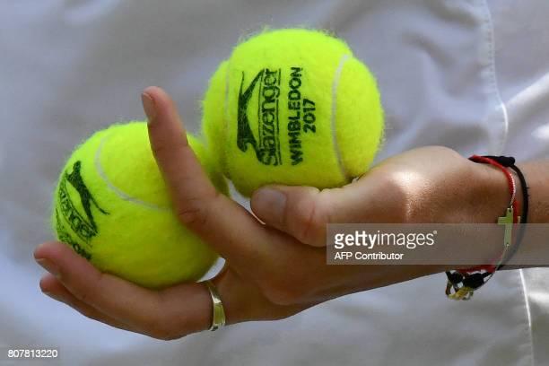 Czech Republic's Karolina Pliskova holds Wimbledonbranded Slazenger tennis balls before serving to Russia's Evgeniya Rodina during their women's...