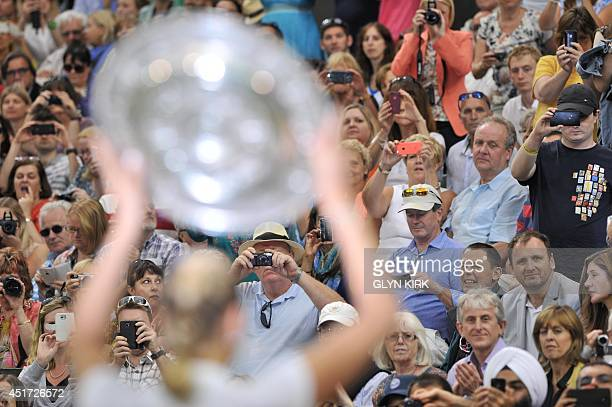 Czech Republic's Petra Kvitova poses for spectators with her winner's Venus Rosewater Dish during the trophy presentation after beating Canada's...
