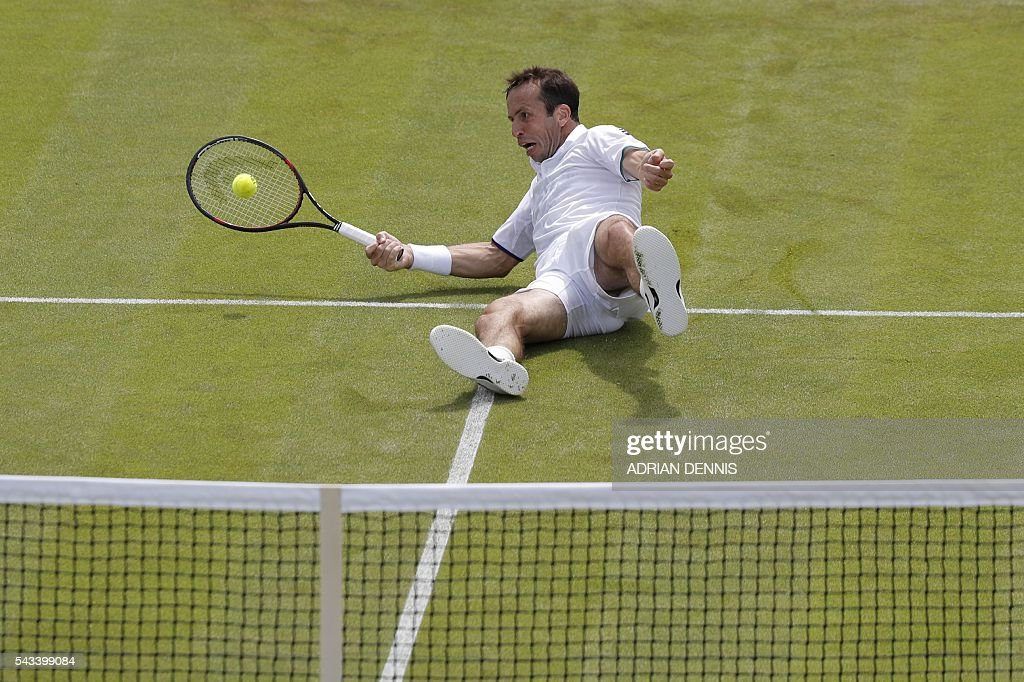 Czech Republic's Radek Stepanek tries to play a shot from the court after losing his footing against Australia's Nick Kyrgios during their men's singles first round match on the second day of the 2016 Wimbledon Championships at The All England Lawn Tennis Club in Wimbledon, southwest London, on June 28, 2016. / AFP / ADRIAN