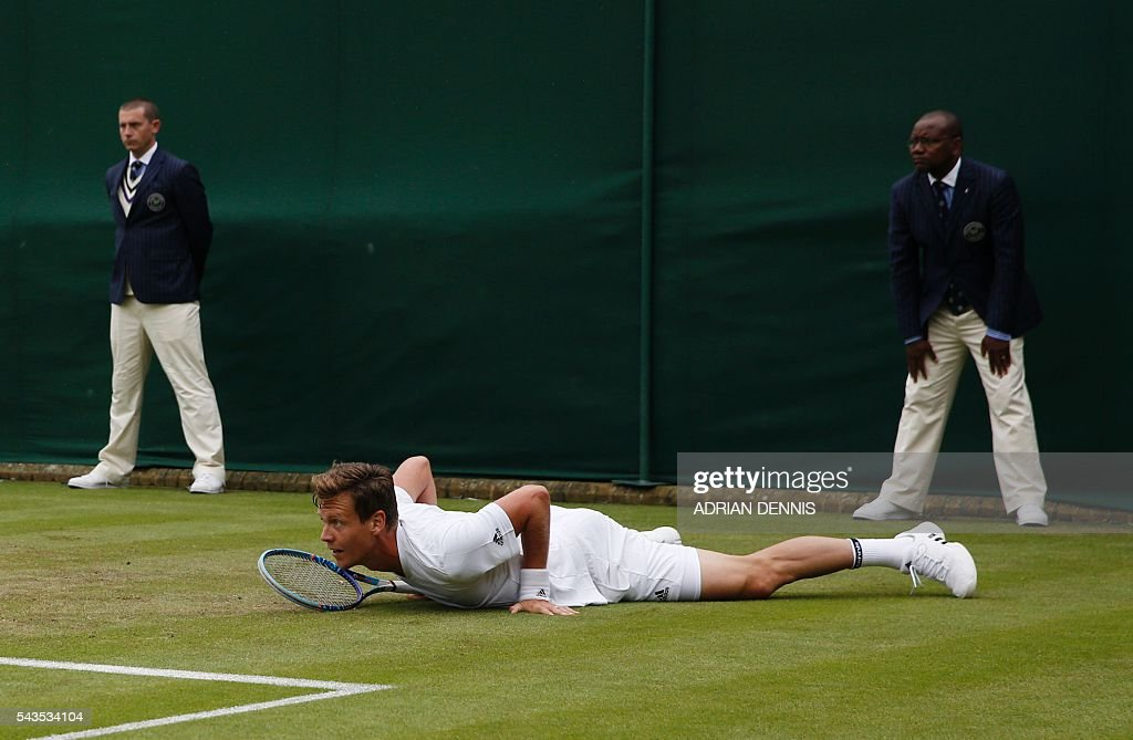 Czech Republic's Tomas Berdych slips as he plays Croatia's Ivan Dodig during a men's singles first round match on the third day of the 2016 Wimbledon Championships at The All England Lawn Tennis Club in Wimbledon, southwest London, on June 29, 2016. / AFP / ADRIAN