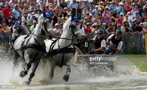 TOPSHOT Czech rider Jiri Nesvacil leads his horses through an obstacle during the Marathon driving competition for fourinhand drivers during the...