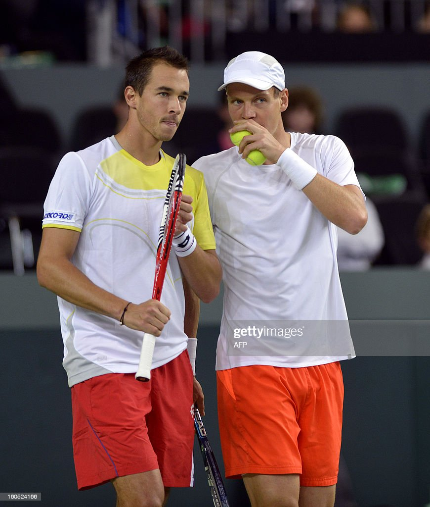 Czech Tomas Berdych (R) and Lukas Rosol chat between two points against Swiss' Stanislas Wawrinka and Marco Chiudinelli in the Davis Cup World Group first round game between Switzerland and title owner the Czech Republic on February 2, 2013 in Geneva.