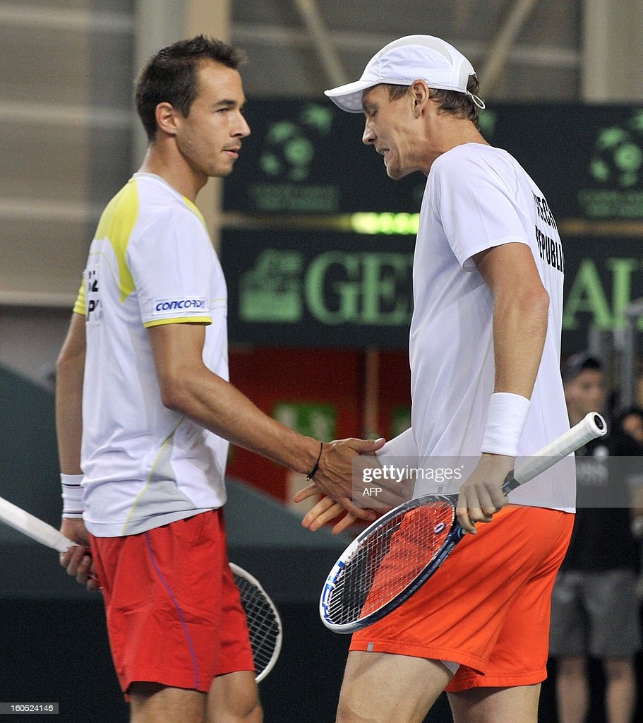 Czech Tomas Berdych (R) and Lukas Rosol clap their hands during a Davis Cup tennis match against Swiss' Stanislas Wawrinka and Marco Chiudinelli in the Davis Cup World Group first round game between Switzerland and title owner the Czech Republic on February 2, 2013 in Geneva.