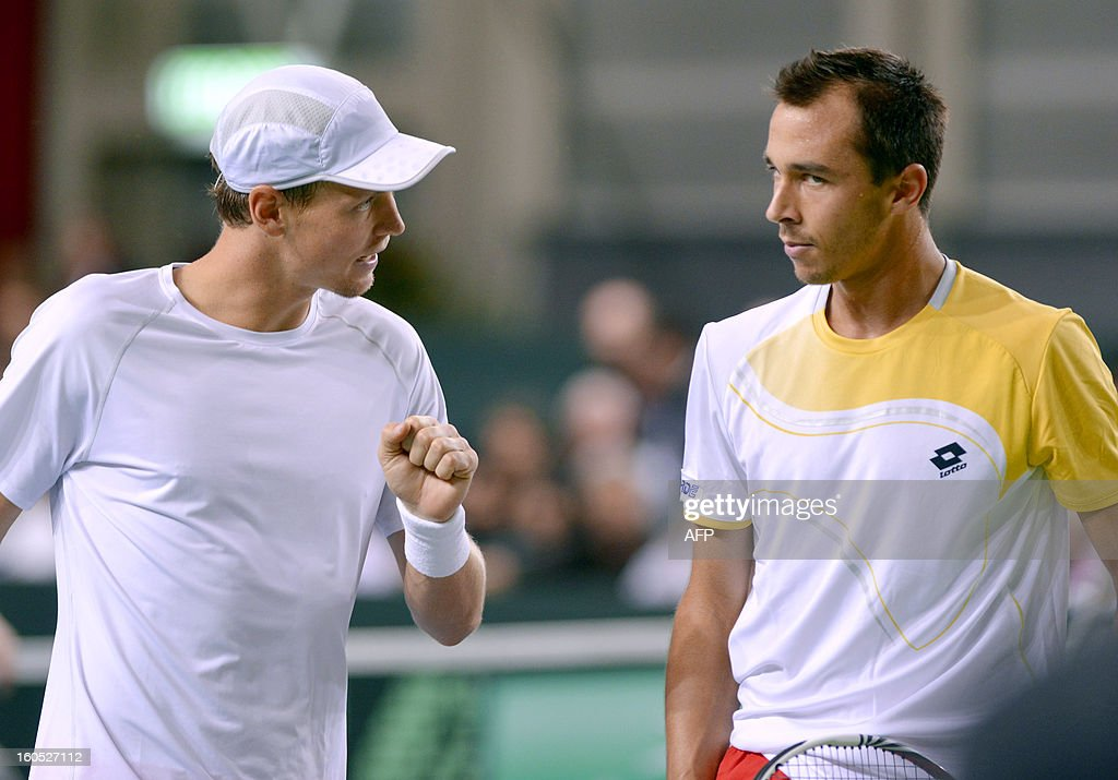 Czech Tomas Berdych (L) and Lukas Rosol speak between two points against Swiss Stanislas Wawrinka and Marco Chiudinelli during a Davis Cup World Group first round tennis match between Switzerland and title owner the Czech Republic on February 2, 2013 in Geneva.