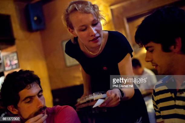 A Czech woman serves two young men the Beer museum central Prague Czech Republic