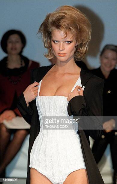Czechborn supermodel Eva Herzigova presents 17 January a white corseted tanktop leotard with embrodered chevrons worn with a hooded black silk...
