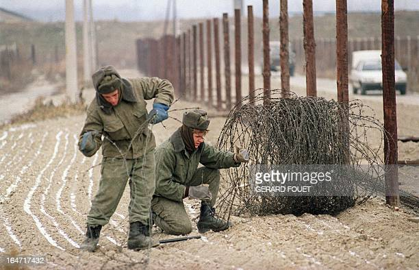 Czechoslovakian border guards dismantle the twometer high barbed wire fence along the border with Austria 11 December 1989 A strong dissident protest...