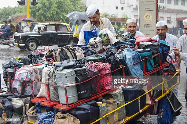 A dabbawala carrying lunch boxes from his home and delivering it to offices in Mumbai Maharashtra India