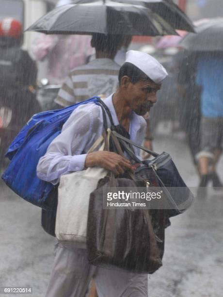 A dabbawala runs as it rains suddenly at Kalbadevi on Thursday