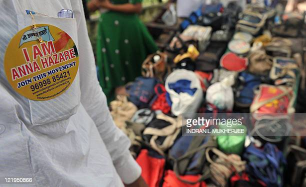 A Dabbawalalunchbox delivery man sports a pinned badge expressing his support to the crusade of veteran Indian activist Anna Hazare to denounce the...