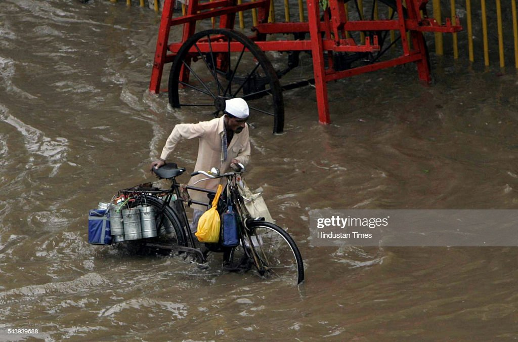 A Dabbawallah wades through knee deep water near Hindmata Cinema, Parel on July 21, 2005 in Mumbai, India. Heavy rains lashed across the city leaving most of the areas around the city in a flooded state.