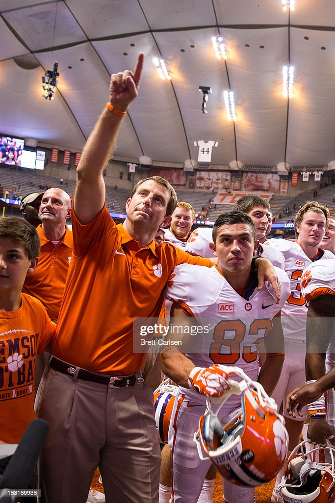 Dabo Swinney, head coach of Clemson Tigers, raises a salute to the Clemson fans following the team's victory over Syracuse Orange on October 5, 2013 at the Carrier Dome in Syracuse, New York. Clemson defeated Syracuse 49-14.