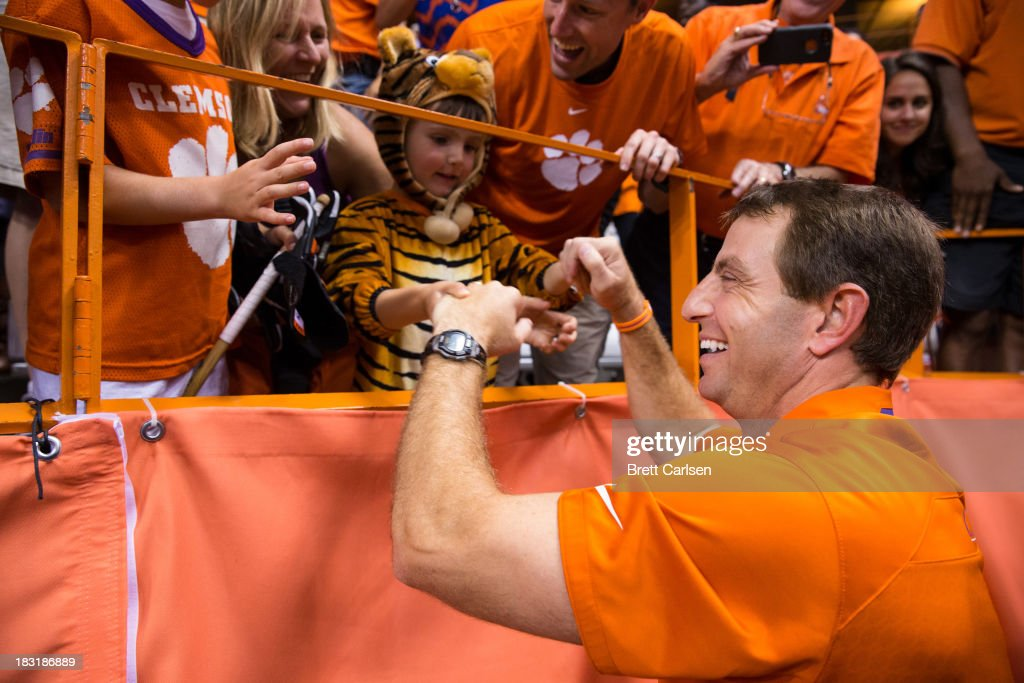 Dabo Swinney, head coach of Clemson Tigers, shakes hands of Clemson fans after defeating Syracuse Orange on October 5, 2013 at the Carrier Dome in Syracuse, New York. Clemson defeated Syracuse 49-14.