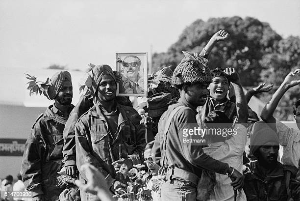 Indian soldiers rejoice 12/16 after entering the capital of East Pakistan One soldier holds up a picture of Awami League chief Sheikh Mujibur Rahman...
