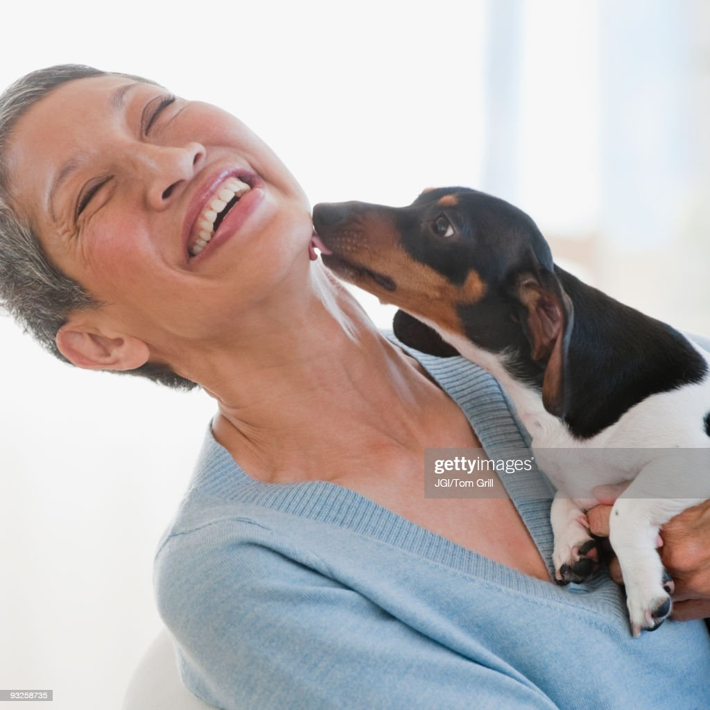Dachshund licking Chinese woman's face