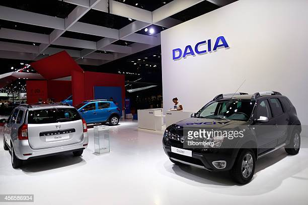 Dacia Logan MCV left and Duster automobiles produced by Renault SA stand on display at the Paris Motor Show on the final preview day in Paris France...