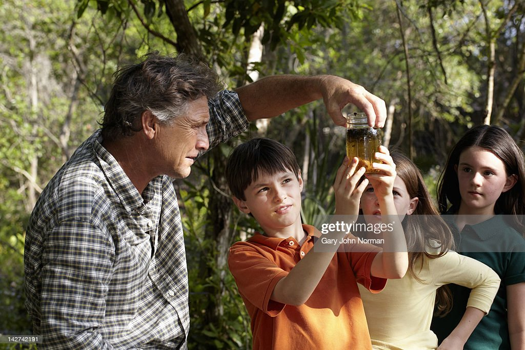 Dad and children look at pond life in jar. : Stock Photo
