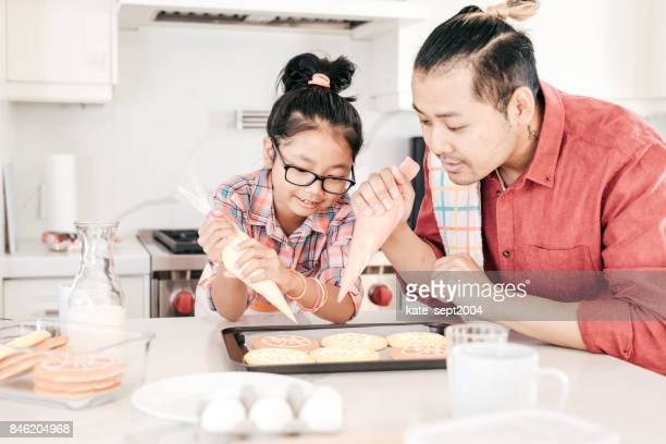 Dad and daughter baking cookies together