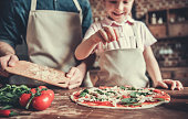 Cute little girl and her handsome dad in aprons are smiling while cooking pizza in kitchen
