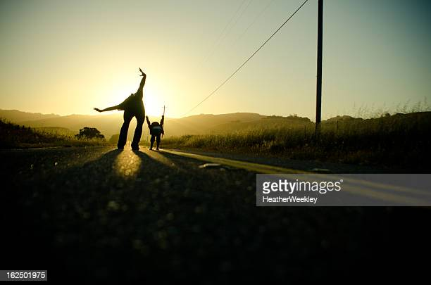 dad and daughter on a road pretending to fly