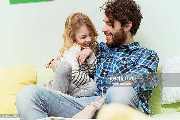 Dad and daughter playing and cuddling on sofa