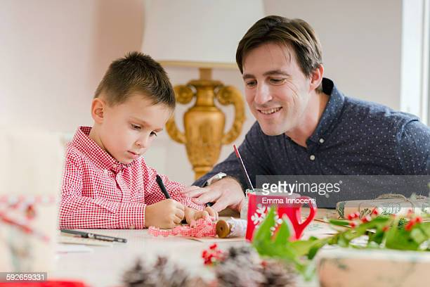 dad and son decorating wrapping brown paper
