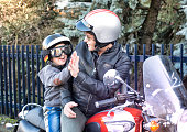 Dad and Son Giving a Five Riding a Motorcycle