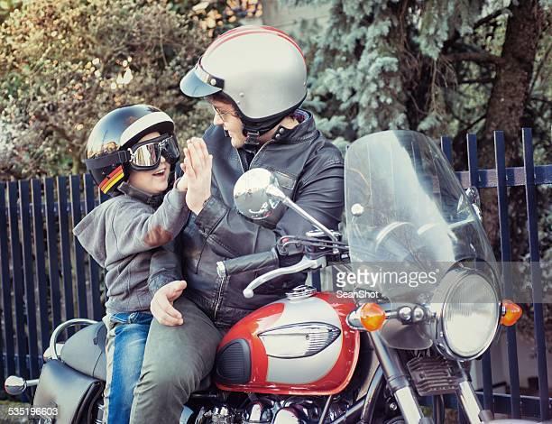 Pai e filho a dar um cinco dirigindo um motociclo