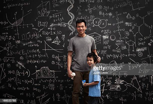 Dad and son in front of math covered chalkboard