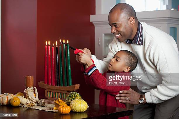 Dad and son lighting Kinara for Kwanzaa