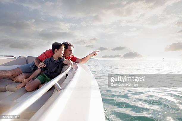 dad and son on motor boat, dad pointing out to see