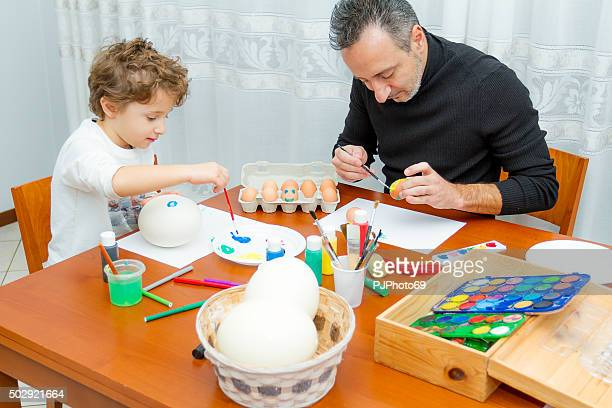 Dad and son painting Easter eggs