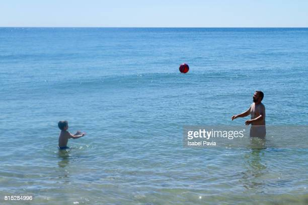 Dad and Son Playing with a Ball in the Sea