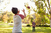 Dad and son throwing American football to each other in park