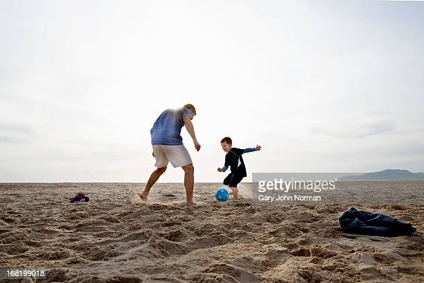 dad and sons playing football on the beach