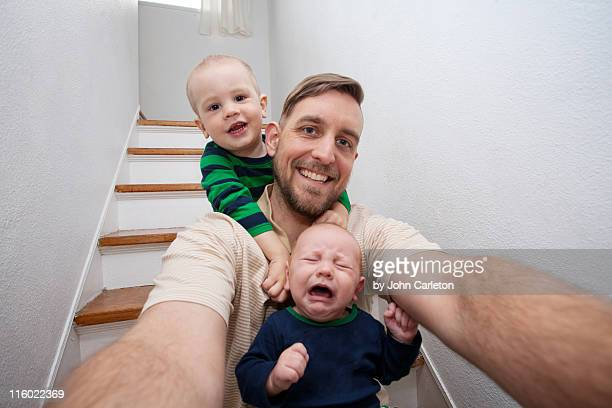 Dad and sons sitting in stairwell