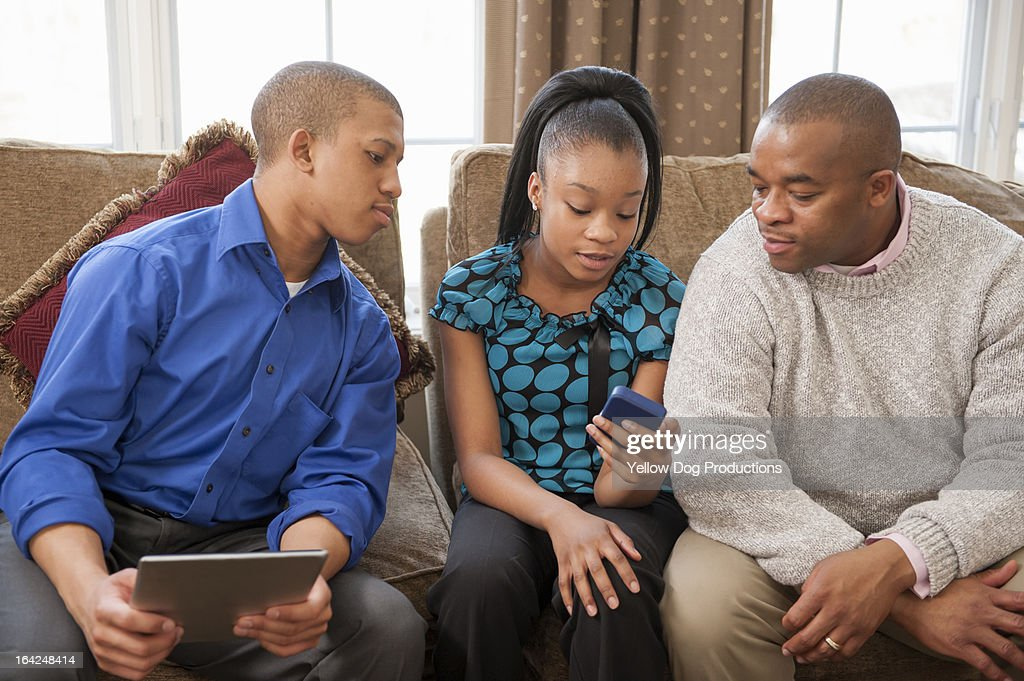 Dad and teen kids at home looking at smartphone : Stock Photo