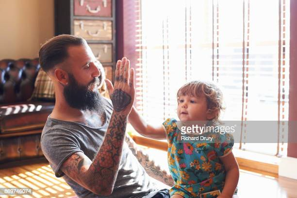 Dad and toddler daughter doing high-five