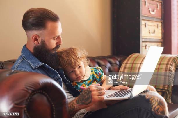 Dad and toddler daughter using laptop