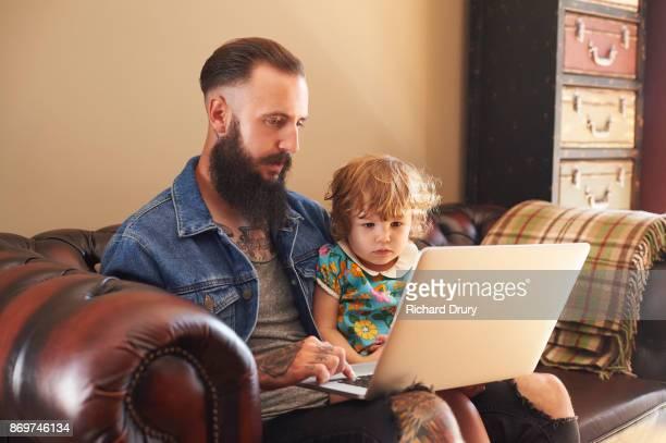 Dad and toddler girl using laptop